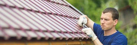 Der Meister macht Reparaturarbeit auf dem Dach, nach links ein leerer Platz für eine Aufschrift stockfotos