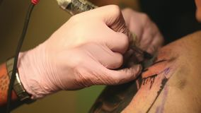 Der Meister malt eine Tätowierung mit einer Zeichnung des Todes auf der Schulter eines Mannes stock video