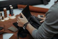 Der Meister stellt eine Ledertasche her Ein Abschluss oben, ein Produkt von der Haut in den Händen Lizenzfreie Stockbilder