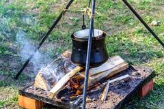 Der Metallgroße kessel, der an einem Stativ über einem offenen Feuer am internationalen Ritterfestival Turnier von St George häng Stockfoto