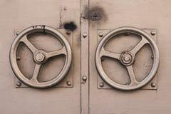 Der metallische Türknauf in Form des vergoldeten Lenkrads Goldene Farbe der alten Tür mit zwei Türrundgriffen lizenzfreies stockbild