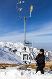 Der Meteorologe, der an einer Wetterstation in den Bergen arbeitet stockbild