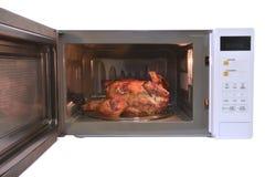 Der Mikrowellenherd ist warmes gebratenes Huhn mit schwarzem Pfeffer Stockfotos