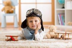 Der mit hölzernem Flugzeug spielende und träumende Kinderbildjunge ist Flieger lizenzfreie stockfotografie