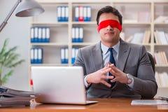 Der mit verbundenen Augen Geschäftsmann, der am Schreibtisch im Büro sitzt Lizenzfreies Stockfoto