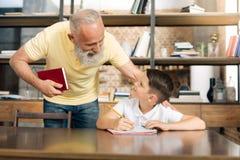 Der mitfühlende Großvater, der seine Enkel überprüft, kommen in Hausarbeit weiter lizenzfreie stockfotos