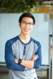 Der männliche Student, der mit den Armen steht, faltete sich in der Universität Stockbild