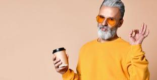 Der moderne Mannsenior, der Kamera, Kappe mit Kaffee in den Armen habend betrachtet und zeigt ein Zeichen-O.K. mit seinen Fingern lizenzfreies stockbild
