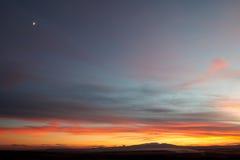 Der Mond über dem Sonnenuntergang Stockbilder
