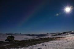 Der Mond mit den Strahlen und den Nordlichtern im blauen Winterhimmel Islands s über einem isländischen Haus, das auf einem Lavaf lizenzfreie stockfotos