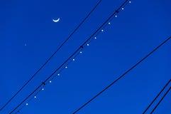 Der Mond und das Venus, silhouettiert mit den Masten USSs Conste Stockfoto