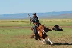 Der mongolische Mann, der traditionelles Kostüm trägt, fährt auf Pferd zurück in eine Steppe in Kharkhorin, Mongolei stockbilder