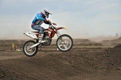 Der Motocross-Rennläufer springt mit dem Motorrad Stockbild