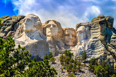 Der Mount Rushmore, bewölkt mit blauen Himmeln Stockfotos