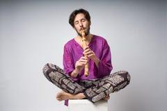 Der Musiker, der ethnische Instrumente spielt Der Mann, der im Lotussitz sitzt, spielt die Flöte Stockfotografie
