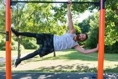 Der muskulöse junge Mann, der Körpergewicht tut, trainiert in einem modernen Eignungspark lizenzfreie stockfotos