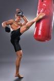 Der muskulöse Kämpfer, der einiges übt, tritt mit Sandsack Stockbild