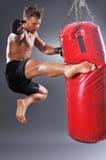 Der muskulöse Kämpfer, der einiges übt, tritt mit Sandsack Stockfotos
