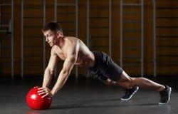 Der muskulöse Mann, der Sport tut, trainiert mit rotem Medizinball Stockfotografie