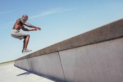 Der muskulöse Mann, der Kasten tut, springt draußen Lizenzfreies Stockfoto