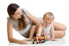 Der Mutter- und Kinderjunge, der Block spielt, spielt zu Hause Stockfotografie