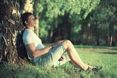 Der nachdenkliche Mann, der nahe einem Baum mit seinem sitzt, mustert das geschlossene Meditieren Lizenzfreie Stockfotos