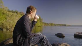 Der nachdenkliche Mann sitzt auf dem großen Stein, der im Fluss liegt und trinkt Kaffee weg aufpassend stock video