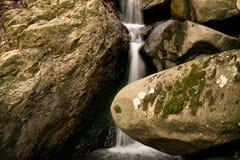 Der natürliche Hintergrund des schönen weichen Flusswasserfallfließens versteckt im Wald schaukelt Lizenzfreie Stockfotos