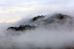 Der Nebel, der über die Berge steigt Stockbild