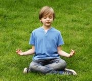 Der nette blonde Junge, der auf Gras sitzt und meditiert Lizenzfreie Stockfotografie