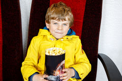 Der nette blonde Kleinkindjunge, der Popcorn am Kino vor dem Film isst, beginnt Stockbilder