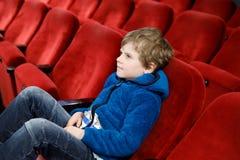 Der nette blonde Kleinkindjunge, der Popcorn am Kino vor dem Film isst, beginnt Lizenzfreie Stockfotografie