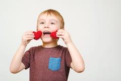 Der nette glückliche Junge, der mit zwei spielt, strickte die roten Herzen, lokalisiert auf weißer Wand, copyspace Stockfotografie
