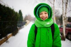 Der nette Jugendliche geht die Straße am Wintertag hinunter Stockfotografie