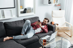 Der nette junge Mann liegt auf Sofa telefonisch plaudernd Stockfotos