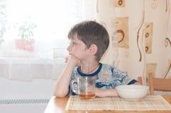 Der nette Junge sitzt an einem Tisch während eines Frühstücks stockfoto