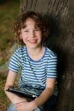 Der nette Junge sitzt unter einem Baum mit Tablette auf Schoss Stockfotografie
