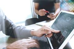 der Netzdesigner mit zwei Kollegen, der Daten besprechen und die digitale Tablette tun Stockfoto