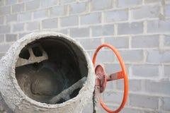 Der neue orange Betonmischer an einer Baustelle Stockfoto