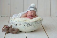 Der neugeborene Junge liegt in einer runden Schüssel auf einem weißen Plaid und schläft Lizenzfreies Stockbild