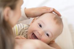 Der neugeborene Zeitraum Mutter, die ihr neugeborenes Kind hält Kleinkind, das Kamera lacht und betrachtet stockbilder