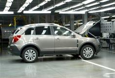 Der Neuwagen mit einer offenen Haube kostet in der Montagewerkstatt automobil Stockfoto