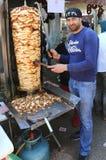 Der nicht identifizierte Kerl, der Huhn-Doner-Kebab mit Klinge schneidet, mögen langes Messer Stockbilder
