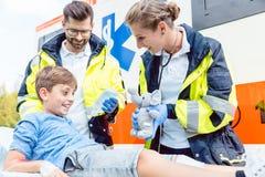 Der Notmediziner, der weiches Spielzeug zur Konsole gibt, verletzte Jungen Lizenzfreie Stockbilder