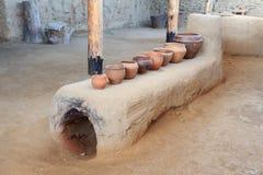 Der Ofen eines Bronzejahrhunderts mit den keramischen Töpfen, die auf ihm stehen stockbilder