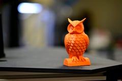Der orange Eulengegenstand, der durch Drucker 3d gedruckt wird, steht auf undeutlichem dunklem Hintergrund Lizenzfreie Stockbilder
