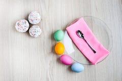 Der Ostern-Kuchen und die bunten Eier auf einer weißen Tabelle Stockfoto