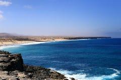 Der Ozean, die Steinklippe, der blaue Himmel und der sandige Strand Lizenzfreie Stockfotos