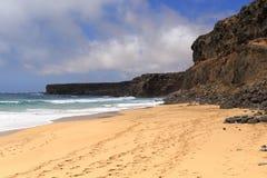 Der Ozean, die Steinklippe, der blaue Himmel und der sandige Strand Lizenzfreies Stockfoto