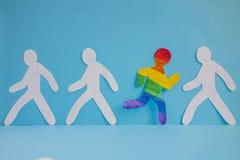 Der Papiermann, der in den Farben der LGBT-Flagge gemalt wird, läuft aus der grauen Masse heraus lizenzfreie stockfotografie